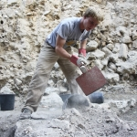 Jessie Hester fills buckets with bone-dry soil.